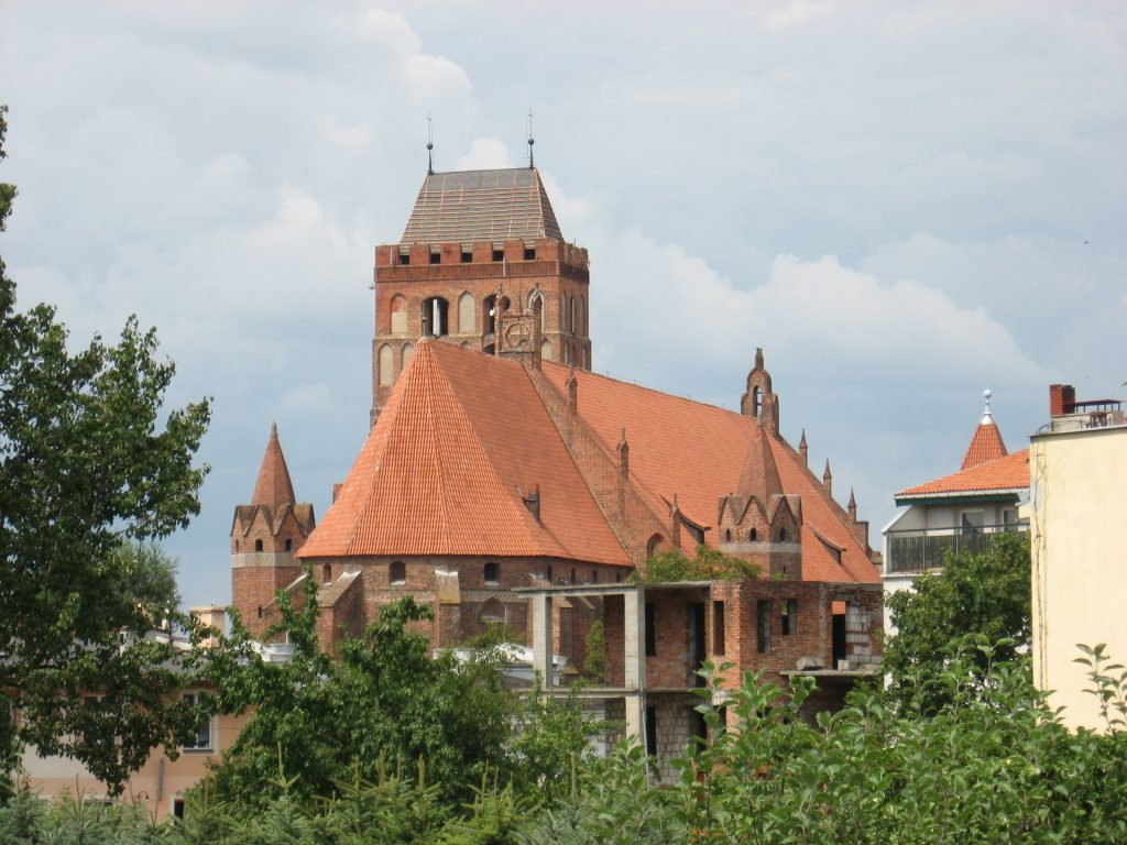 Red-brick cathedral with orange-red roof surrounded by trees