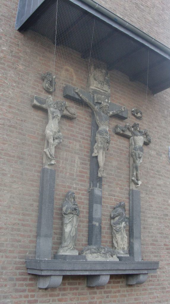 Sixteenth-century group of statues of the Crucifixion, affixed to modern brick wall